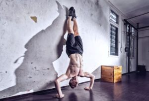 a man does Handstands in the gym