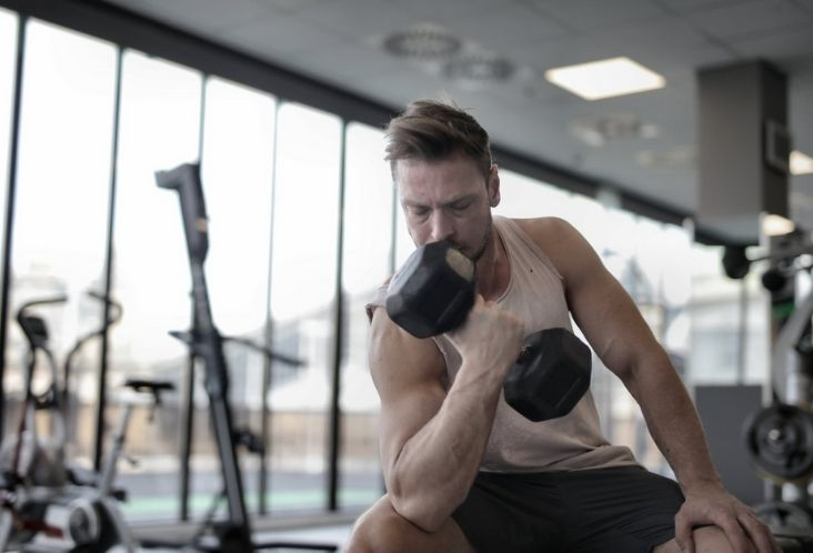 determined muscular man exercising with dumbbell