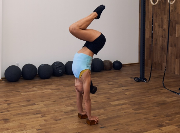a woman using a handstand blocks in a gym